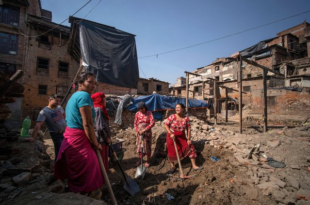 Bidhya Laxmi Prajapati, 45, (R) smiles as she works with a pick axe as she clears debris at her former house damaged during the April 2015 earthquake, together with family and neighbours on April 24, 2016 in Kathmandu, Nepal. Bidhya recently started rebuilding her house which collapsed during last year's earthquake after deciding not to wait any further for compensation promised by the government. (Photo by Tom Van Cakenberghe/Getty Images)