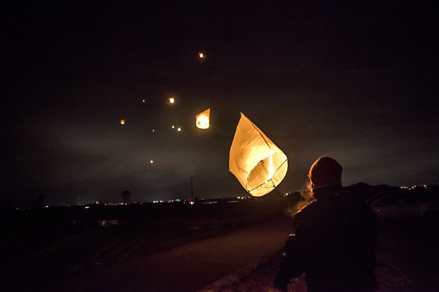 A man watches as his paper lantern, lit in commemoration of the victims of last year's earthquake and tsunami, floats away into the distance on March 11, 2012 in Natori, Japan. On the one year anniversary, the areas most affected by last year's March 11, 2011 earthquake and subsequent tsunami that left 15,848 dead and 3,305 missing according to Japan's National Police Agency, continue to struggle. Thousands of people still remain without homes living in temporary dwellings. The Japanese government faces an uphill battle with the need to dispose of rubble as it works to rebuild economies and livelihoods. Across the country people are taking part in ceremonies to pay respects to the people who lost their lives. (Photo by Daniel Berehulak/Getty Images)