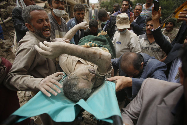 People carry the body of a man they uncovered from under the rubble of houses destroyed by Saudi airstrikes in the old city of Sanaa, Yemen, Friday, June 12, 2015. (AP Photo/Hani Mohammed)