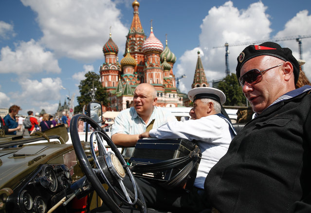 People by a vintage car during the 2019 GUM Motor Rally featuring classic cars in Moscow, Russia on July 28, 2019. The rally includes cars such as the ZIL, the Chaika, the Volga, Zaporozhets, Pobeda, Moskvich and the Zhiguli. (Photo by Artyom Geodakyan/TASS via Getty Images)