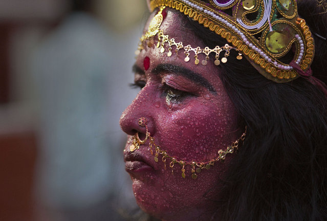 Indian woman Anjali Mahanta, 48, sweats, as she stands dressed as Hindu goddess Kali anticipating alms from devotees at the Kamakhya Hindu temple during the annual Ambubasi festival in Gauhati, India, Wednesday, June 24, 2015. Hundreds of Hindu holy men have arrived here to perform rituals during the five-days long festival that began Monday. (Photo by Anupam Nath/AP Photo)