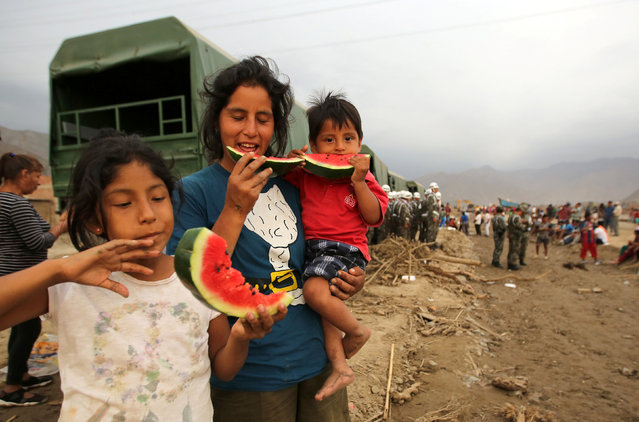 Survivors of a flood receive food after torrential rains caused flooding and widespread destruction in Huachipa, Lima, Peru, March 18,  2017. (Photo by Mariana Bazo/Reuters)