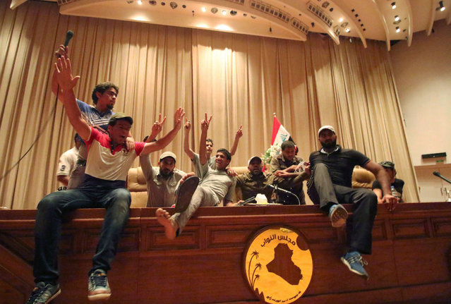 """Iraqi protesters flash the V-sign as they gather inside the parliament after breaking into Baghdad's heavily fortified """"Green Zone"""" on April 30, 2016. A protest held outside the Green Zone escalated after parliament again failed to reach a quorum and approve new ministers to replace the current government of party-affiliated ministers. (Photo by Haidar Mohammed Ali/AFP Photo)"""