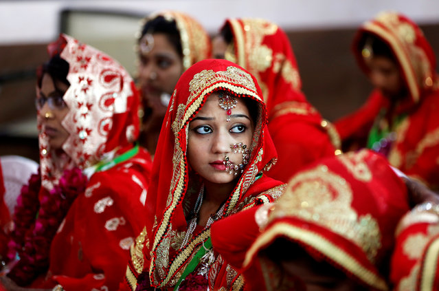 Brides sit and wait for their turn during a Muslim mass wedding in Ahmedabad, March 12, 2017. (Photo by Amit Dave/Reuters)