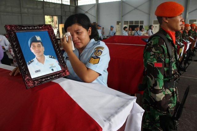 A relative of military personnel grieves during a send-off ceremony at the military airbase in Medan on July 1, 2015, a day after an Indonesian Air Force C-130 Hercules plane crashed into a residential area of the city shortly after takeoff. (Photo by AFP Photo/ATAR)