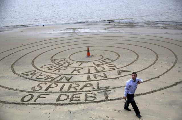 A man walks away after drawing a spiral in exposed sand next to the River Thames during low tide, near the South Bank in London, Britain May 2, 2016. (Photo by Neil Hall/Reuters)