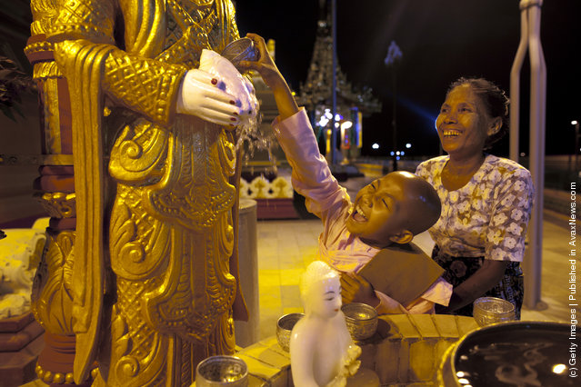 A young Burmese nun gives a traditional blessing by pouring water on Buddha statue at the Ouparta Thandi  pagoda