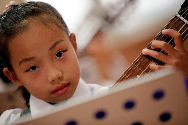 A girl plays the guitar at the Mangyongdae Children's Palace in Pyongyang, North Korea May 5, 2016. (Photo by Damir Sagolj/Reuters)