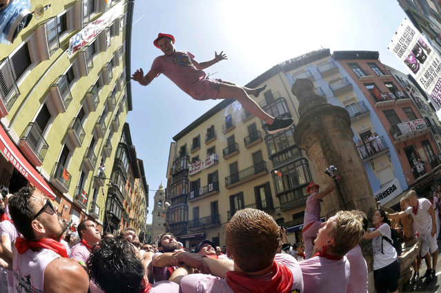 Revelers gathered on City Hall Square celebrate after the firing of the 'txupinazo' rocket which marked the official beginning of the Fiestas de San Fermin in Pamplona, Spain, 06 July 2015. The festival, locally known as Sanfermines, is held annually from 06 to 14 July in commemoration of the city's patron saint. Photo by Daniel Fernandez/EPA)