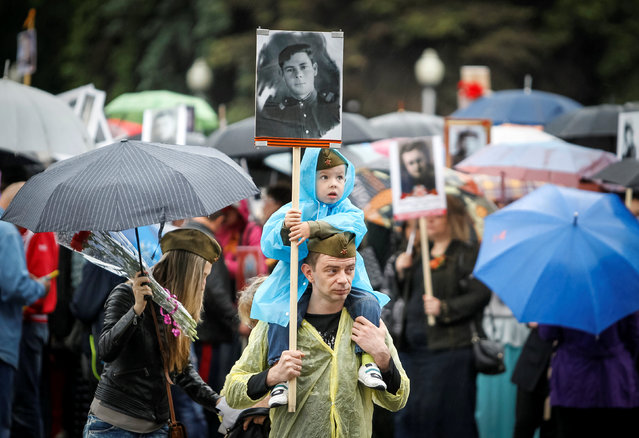 A man with his child hold a portrait of their deceased relative who took part in World War Two during a march at Victory Day commemorations in  Almaty, Kazakhstan, May 9, 2016. (Photo by Shamil Zhumatov/Reuters)