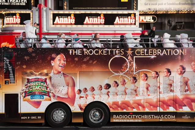 Tourists wearing white rain coats ride a bus covered with an ad of The Rockettes in Times Square in New York, October 9, 2012. (Photo by Natan Dvir/Polaris)