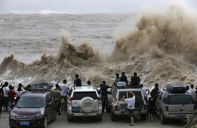 People look on as waves, under the influence of Typhoon Chan-hom, hit the shore in Wenling, Zhejiang province, China, July 10, 2015. More than 865,000 people have been evacuated from China's eastern province of Zhejiang ahead of Saturday's expected landfall of Typhoon Chan-Hom, state news agency Xinhua said. (Photo by William Hong/Reuters)