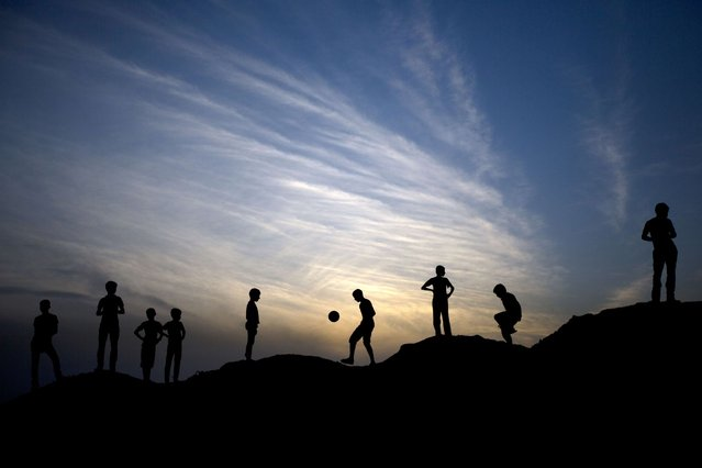 A picture taken on May 4, 2014 at sunset shows Palestinian boys playing football in Beit Lahia in the northern Gaza Strip. (Photo by Mahmud Hams/AFP Photo)
