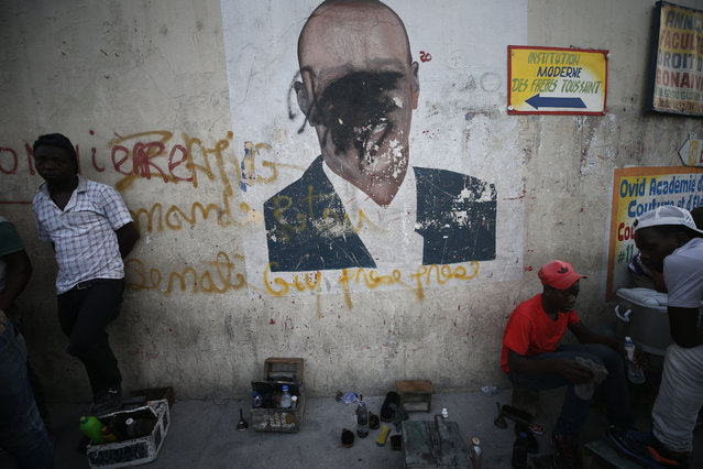 A man shines a client's shoes as another waits for business, in front of a wall painted with an image of President Jovenel Moise, his face obscured by black spray paint, in the Delmas neighborhood of Port-au-Prince, Haiti, Tuesday, October 8, 2019. The country has entered its fourth week of anti-government protests that have paralyzed the economy and shuttered schools as demonstrators demand the resignation of the president. (Photo by Rebecca Blackwell/AP Photo)