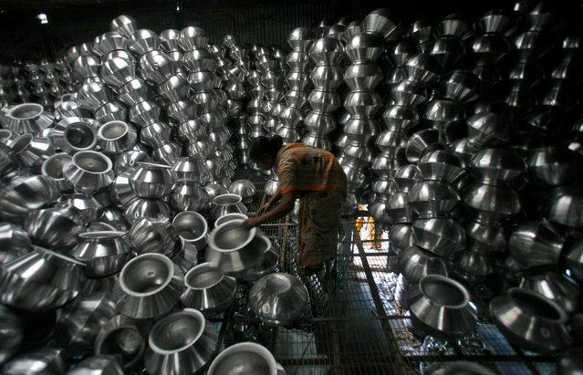 A worker checks aluminium utensils inside a factory on the outskirts of Agartala, capital of India's northeastern state of Tripura October 12, 2012. (Photo by Jayanta Dey/Reuters)