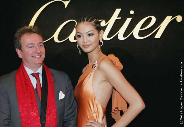 President of Cartier International poses for pictures with a model displaying Cartier jewels during the opening ceremony of Cartier's new flagship store