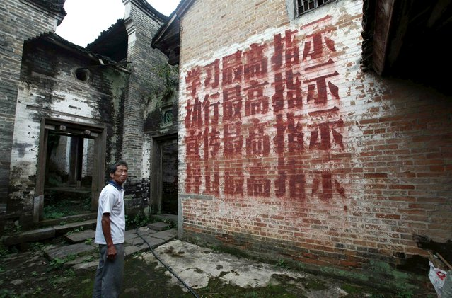 """A villager stands in front of a house where revolutionary slogans are painted on the wall in Dongzhai village, Guangxi Zhuang Autonomous Region, China, July 19, 2015. The slogan on the wall reads: """"Learn from the supreme instructions, execute the supreme instructions, promote the supreme instructions and defend the supreme instructions"""". (Photo by Reuters/Stringer)"""