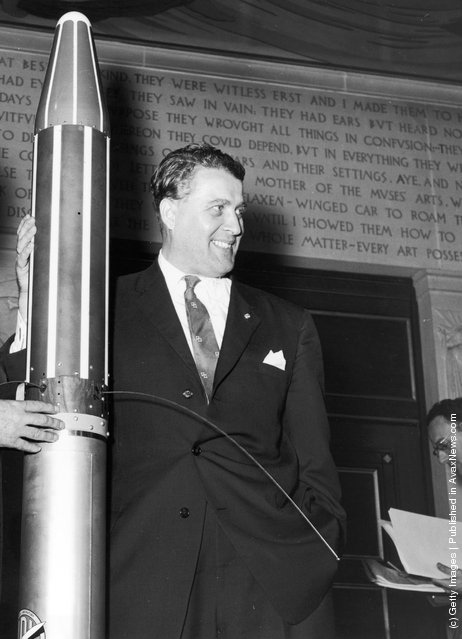 German-born American engineer Dr Wernher von Braun (1912 - 1977) with a model of the Explorer orbiting space satellite which he designed, 1958