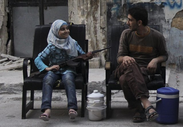 A girl holds a gun across her lap, as she sits with a Free Syrian Army fighter along a street in Aleppo on August 1, 2013. Picture taken August 1, 2013. (Photo by Loubna Mrie/Reuters)