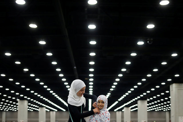 Salma Selenica, 12, (L) adjusts the headscarf of her sister Layla, 8, ahead of the jenazah, an Islamic funeral prayer, for the late boxing champion Muhammad Ali in Louisville, Kentucky, U.S. June 9, 2016. (Photo by Adrees Latif/Reuters)