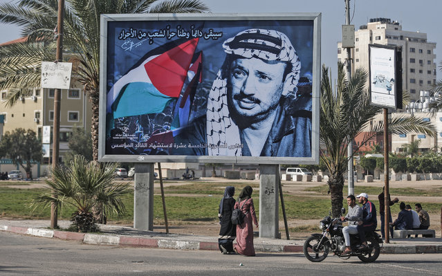 Palestinians walk past a billboard commemorating the 15th anniversary of the death of late Palestinian leader Yasser Arafat near his home in Gaza city, on November 11, 2019. (Photo by Mahmud Hams/AFP Photo)