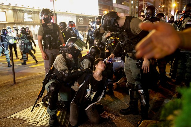 Riot police officers pour water over a pepper sprayed protester as he is detained during an anti-government protest in front of a police station in Mong Kok district, Hong Kong, China on October 7, 2019. (Photo by Jorge Silva/Reuters)