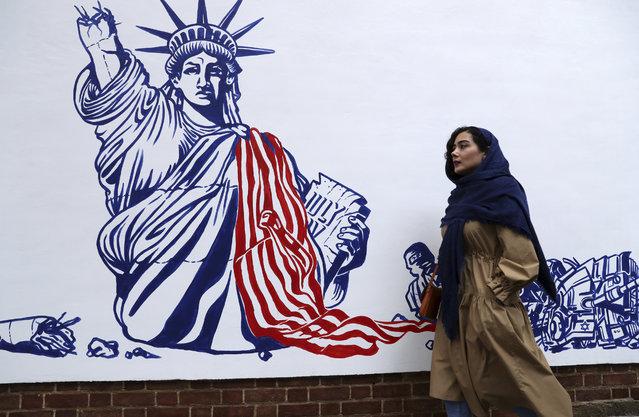 A woman walks past a satirical drawing of the Statue of Liberty after new anti-U.S. murals on the walls of former U.S. embassy unveiled in a ceremony in Tehran, Iran, Saturday, November 2, 2019. Anti-U.S. works of graphics is the main theme of the wall murals painted by a team of artists ahead of the 40th anniversary of the takeover of the U.S. diplomatic post by revolutionary students. (Photo by Vahid Salemi/AP Photo)