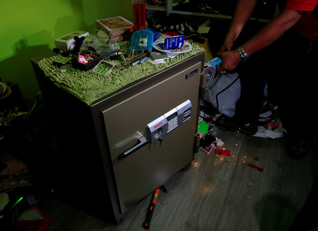 A National Bureau of Investigation agent uses a metal grinder to open a vault that contained drugs and around 7 million pesos in cash during a raid at the home of a police officer and member of the drugs unit in metro Manila, Philippines May 25, 2016. (Photo by Romeo Ranoco/Reuters)