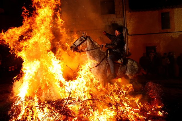 """A rider goes through flames during the annual """"Luminarias"""" celebration on the eve of Saint Anthony's day, Spain's patron saint of animals, in the village of San Bartolome de Pinares, northwest of Madrid, Spain, January 16, 2020. (Photo by Juan Medina/Reuters)"""
