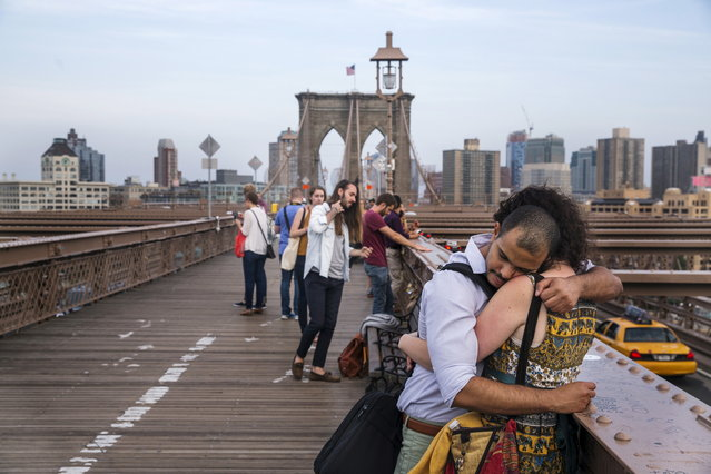A couple embrace as they stand on the Brooklyn Bridge at dusk in New York June 8, 2015. (Photo by Lucas Jackson/Reuters)