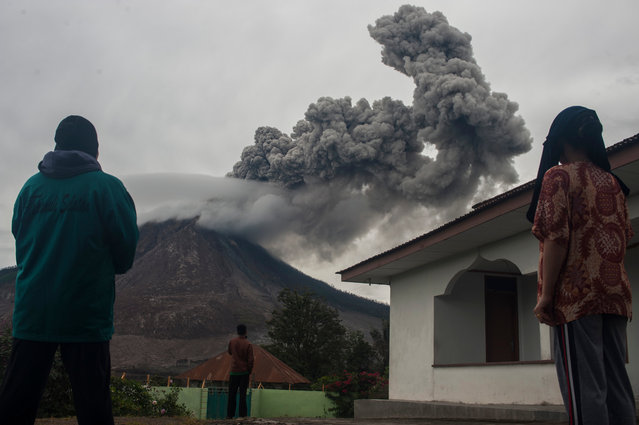 Residents watch the Sinabung volcano during an eruption in Karo, North Sumatra, Indonesia on June 22, 2016. (Photo by Sutanta Aditya/Barcroft Images)