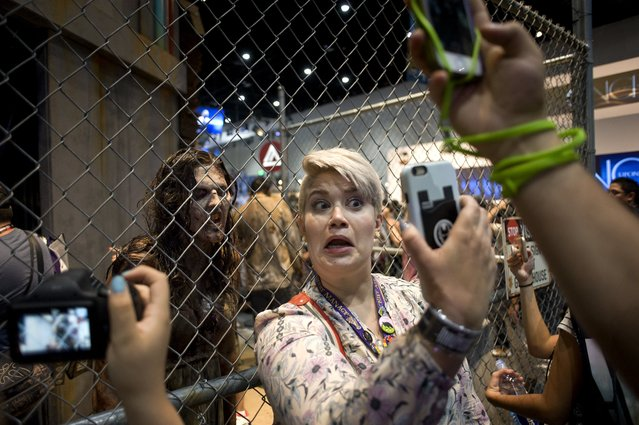 A woman takes a selfie next to a display area for The Walking Dead TV series during the preview night for Comic Con 2017 in San Diego, California, USA, 19 July 2017. (Photo by David Maung/EPA)