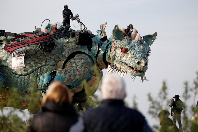 """People look at the """"Dragon de Calais"""" by Francois Delaroziere and La compagnie La Machine during a rehearsal in the harbour of Calais, France on October 30, 2019. (Photo by Pascal Rossignol/Reuters)"""