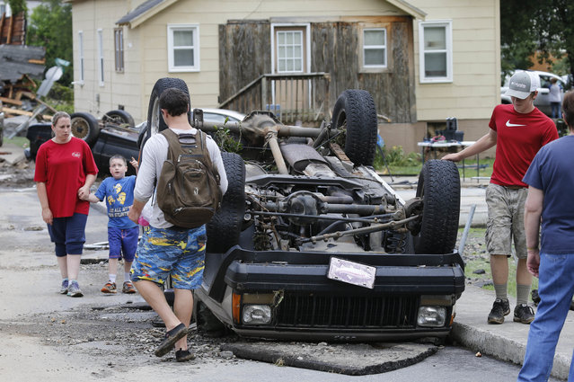 Residents walk past an overturned car as the cleanup begins from severe flooding in White Sulphur Springs, W. Va., Friday, June 24, 2016. (Photo by Steve Helber/AP Photo)
