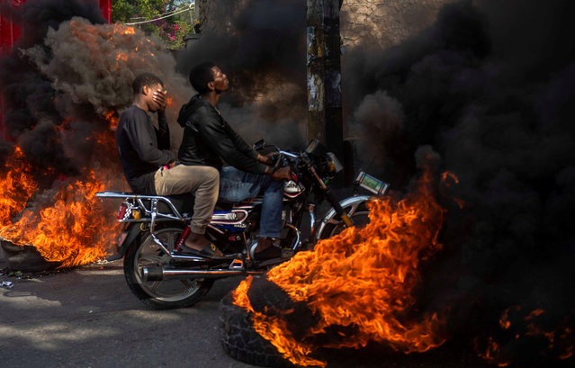 A motorcycle rides among tires burning as part of a march to demand the resignation of President Jovenel Moise, in Port-au-Prince, Haiti, 10 November 2019. Haiti has gone through a new popular uprising sparked by a fuel shortage in the context of a country plagued by corruption, inequality, insecurity and hunger. (Photo by Jean Marc Havelard/EPA/EFE)