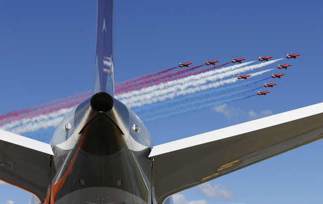 The Royal Air Force (RAF) Red Arrows aerobatic display team perform a fly past Farnborough Airport to open the International Air Show, Farnborough, England, Monday, July 14, 2014. (Photo by Sang Tan/AP Photo)