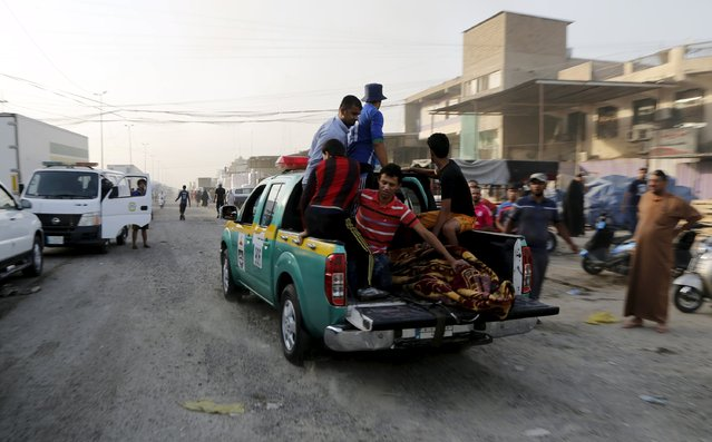 An Iraqi security forces vehicle carrying the body of a victim who was killed at the site of a truck bomb attack at a crowded market in Baghdad August 13, 2015. (Photo by Wissm Al- Okili/Reuters)