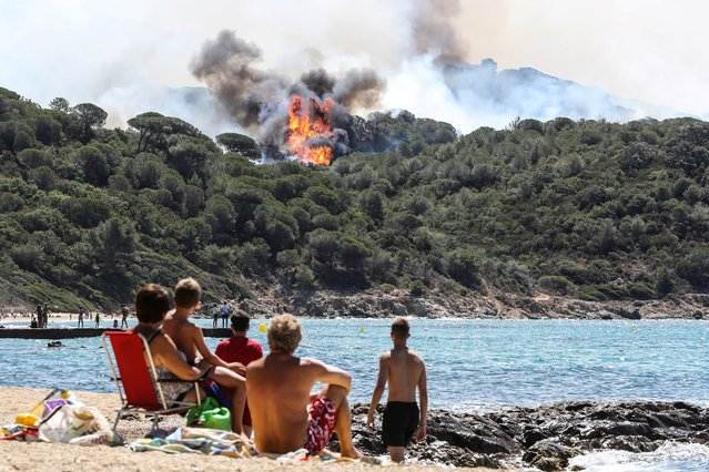 People enjoy the beach as they look at a forest fire in La Croix-Valmer, near Saint-Tropez, on July 25, 2017. Firefighters battle blazes that have consumed swathes of land in southeastern France for a second day, with one inferno out of control near the chic resort of Saint-Tropez, emergency services say. (Photo by Valery Hache/AFP Photo)