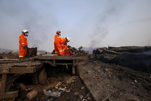 Firefighters wearing gas masks try to put out a fire at the site of Wednesday night's explosions in Binhai new district of Tianjin, China, August 15, 2015. (Photo by Reuters/China Daily)