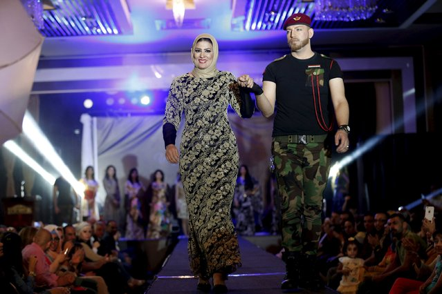 Iraqi designer Waffa Al-Shathar (front, on L) walks out with a model during a fashion show of her creations at the Hunting Club in Baghdad August 13, 2015. (Photo by Thaier al-Sudani/Reuters)