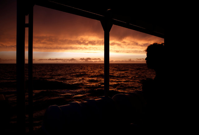 A crew member on the Migrant Offshore Aid Station (MOAS) ship Topaz Responder watches the sunset as the ship stands by for migrants in distress in international waters off the coast of Libya, June 21, 2016. (Photo by Darrin Zammit Lupi/Reuters)