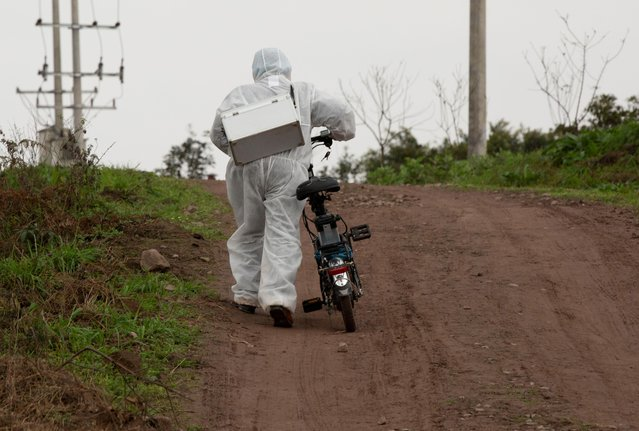 A medical worker in a protective suit pushes his electric bicycle up a hill as he visits villagers for body temperature measurements at a village in Luzhou, Sichuan province, February 10, 2020. (Photo by Reuters/China Daily)