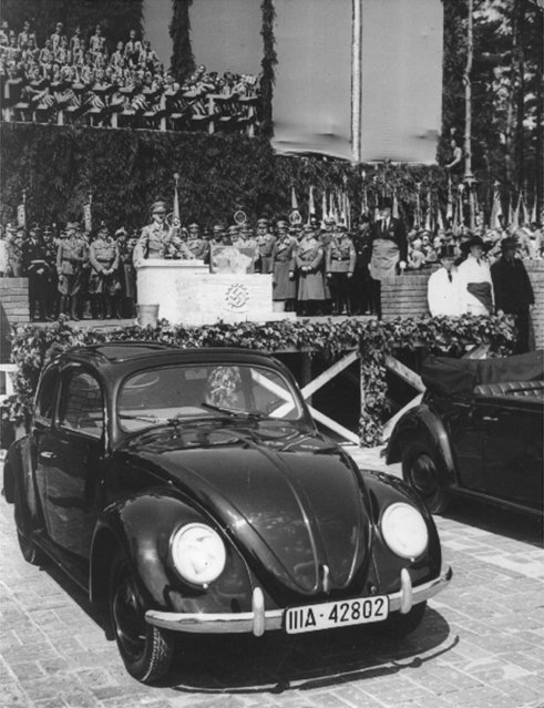 Fallersleben near Hannover, Germany, May 26, 1938. After a speech of Adolf Hitler, the Fuehrer, laid the cornerstone for the giant automobile-works-to-be which are to turn out the cheap peoples car-supposed to be the cheapest car of the world. Photo shows Hitler during his speech. Second at right of him is Dr. Porsche, the constructor of the Volkswagen, first models of which can be seen in the foreground. (Photo by AP Photo)