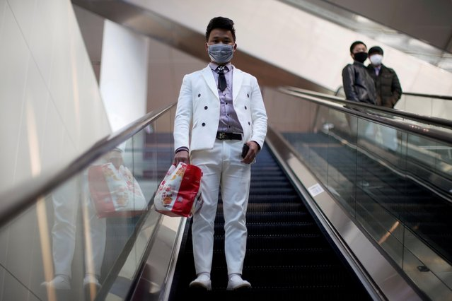 A man wearing a face mask rides an escalator at the Shanghai Hongqiao Railway Station on the last day of the Spring Festival travel rush, as the country is hit by an outbreak of the novel coronavirus, in Shanghai, China February 18, 2020. (Photo by Aly Song/Reuters)