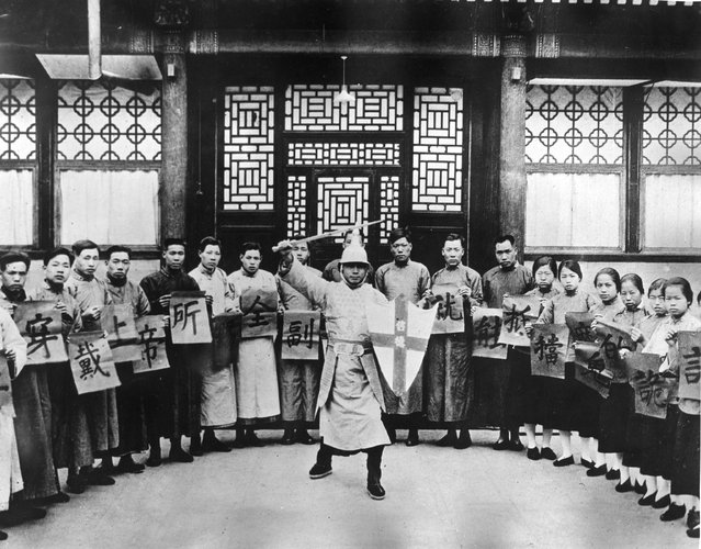 1930: Declared to be Salvation Army recruits in training for officership. They are holding up cards with Chinese symbols as they watch a sword wielding character in military uniform carrying a shield with a cross on it