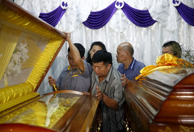 Neoh Hock Guan (C), injured in Monday's blast in Bangkok, views the coffins of his wife and son who were killed in the attack, at his home in Butterworth, Malaysia, August 20, 2015. (Photo by Olivia Harris/Reuters)