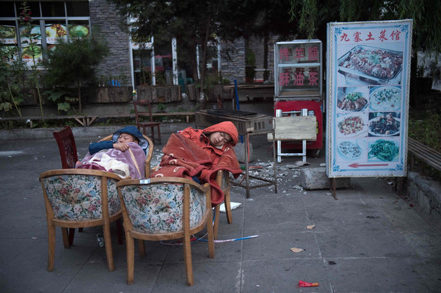 Residents fearing aftershocks sleep outside of their homes after an earthquake in Zhangzha in southwest China's Sichuan province on August 10, 2017. The 6.5-magnitude earthquake struck Sichuan province late on August 8, tearing cracks in mountain highways, triggering landslides, damaging buildings and sending panicked residents and tourists fleeing into the open. (Photo by Nicolas Asfouri/AFP Photo)