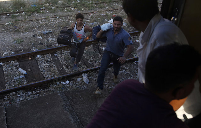 Two migrants try to rush on a train that is passing through Macedonia toward the Serbian border near the southern Macedonian town of Demir Kapija, Wednesday, August 19, 2015. (Photo by Darko Vojinovic/AP Photo)
