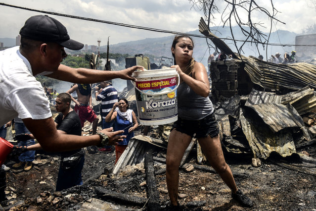 Local residents fight a wild fire in the Moravia neighborhood in Medellin on August 18, 2017. The Moravia sector is known for having been built on a garbage dump and for being the base for late drug lord Pablo Escobar's first political campaign and where he helped to build a football field and to install the electric network. (Photo by Joaquin Sarmiento/AFP Photo)