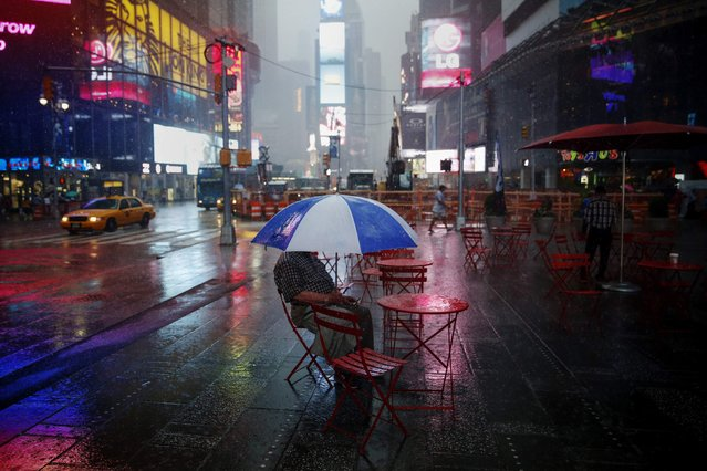 A man sits with an umbrella during a rainstorm at Times Square in New York July 15, 2014. (Photo by Shannon Stapleton/Reuters)